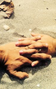 entwined fingers in the sand